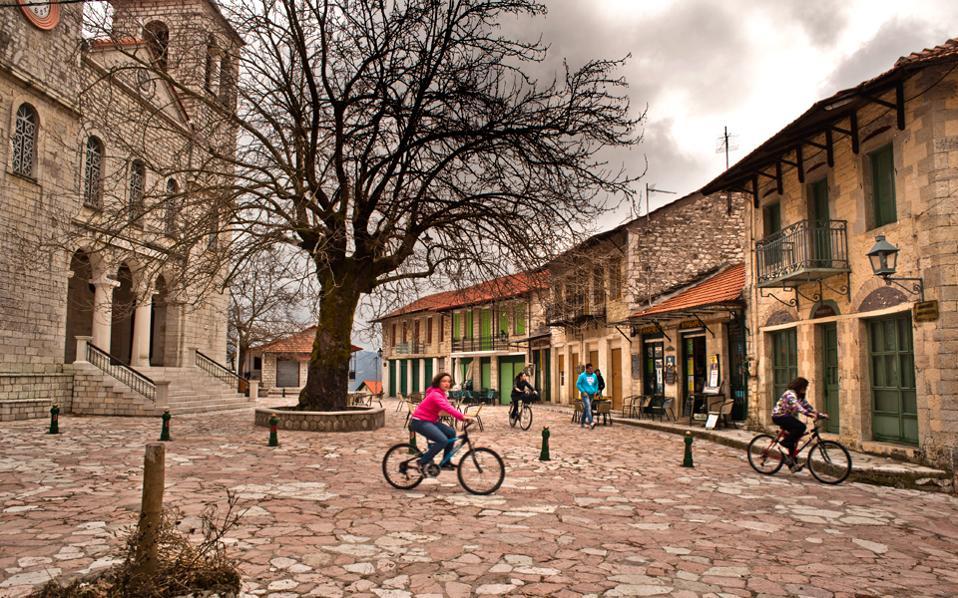 Οι πιτσιρικάδες κάνουν ποδήλατο στην πλακόστρωτη κεντρική πλατεία του Πλατάνου. Η εκκλησία του Αγίου Νικολάου δεσπόζει στα αριστερά.