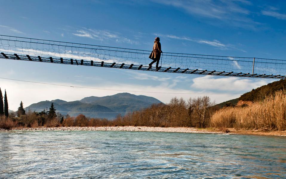 Ισορροπώντας στη συρματογέφυρα, οι λάτρεις της περιπέτειας περνούν από τη μία όχθη του Ευήνου στην άλλη.