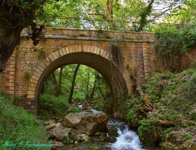 Το πέτρινο γεφύρι των Πηγών Μυρτιάς σε ανοιξιάτικο φόντο